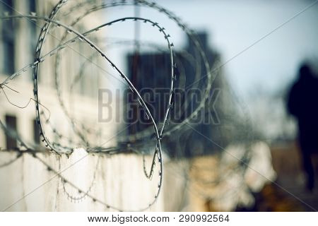 Sharp Barbed Wire At The Top Of The Fence In The Foreground And The Dark Figure Of The Prisoner In T