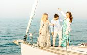 Best friends dancing and having fun on exclusive luxury sailing boat - Friendship travel concept with young people millenial sharing time together on party trip cruise - Bright color tone filter poster