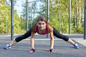 Young caucasian woman workouts on the park sportsground. Active strenght and stretching, bright sportswear. White earphones, protective gloves. Real woman morning training, ironic look. Outdoors. poster
