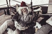 Homeless old man reading book he found with enthusiasm. poster