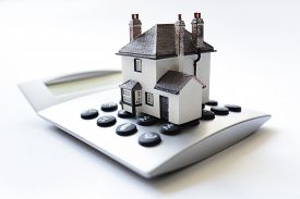 House on calculator concept for mortgage calculator, home finance or saving for a house loan