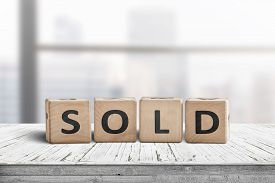 Sold Sign On A Wooden Table With A Bright Windows In The Background