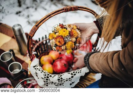 Decor On The Snow In The Winter Park. Basket With Cookies, Fruits, Hot Tea, Coffee On A Blanket At T