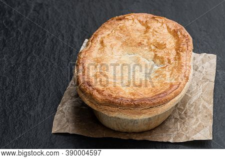 Homemade  Flaky Pasty With Steak And Ale Gravy Filling On Black Stone Background