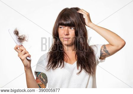 Portrait Of A Sad Woman With Tattoos, Holding A Comb With A Tuft Of Torn Hair. White Background. The