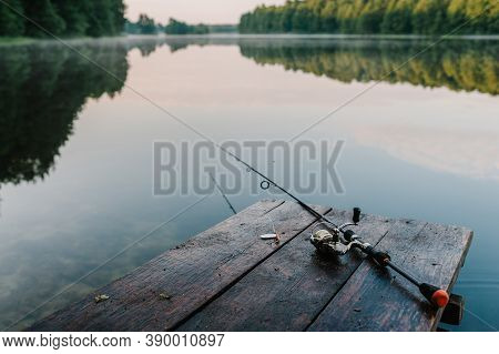 Fishing Rod, Spoon, Hooks On A Brown Wooden Background. Fishing Bait. Close Up. Throw-line. Fishing