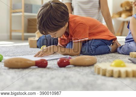 Preschooler Drawing A Picture With Pencils Sitting On Warm Rug With His Brother And Nanny