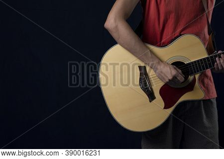 Musician Wearing Red Shirts Playing Acoustic Guitar In The Dark, Copy Space.