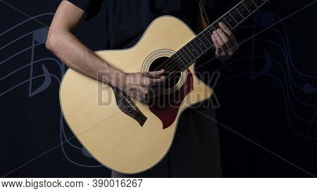 Musician With An Acoustic Guitar In The Dark, Night Photo With Side Lighting.