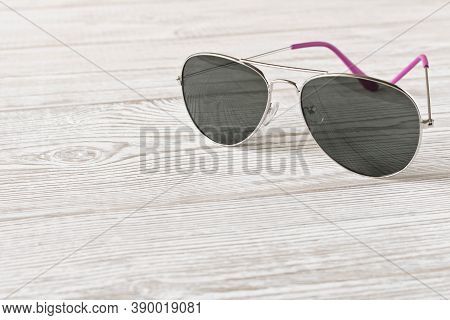 Sunglasses On A Wooden Table. Close Up