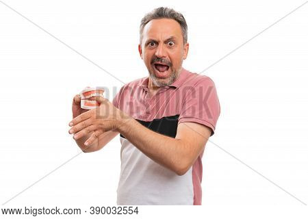 Fake Teeth Denture Prothesis Biting Thumb Finger Of Adult Male Model Making Hurt Expression With Bla