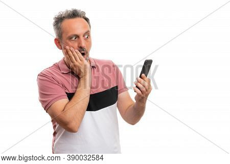 Adult Man Model With Shocked Surprised Expression Looking At Video Or Image On Mobile Telephone Smar