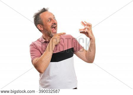 Adult Man With Scared Expression Screaming As Pointing Index Finger At Fake Denture Teeth Prothesis