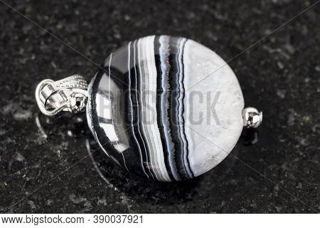 Pendant From Striped Agate Gemstone On Black Granite Background
