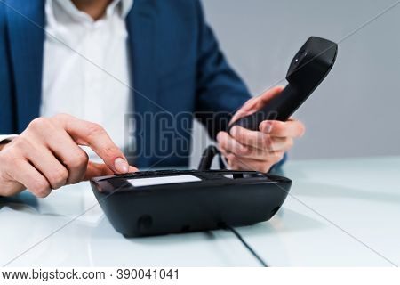 Businessman's Hand Dialing Telephone Number To Make Phone Call In Office