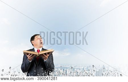 Surprised Businessman Holding Open Old Book And Looking Up. Startled Man In Business Suit And Tie St