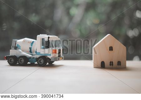 Concrete Mixer Truck Plastic Toy And Miniature Wood Home. Concept Of Construction Home
