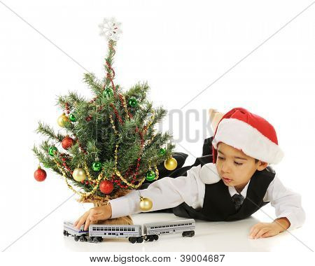 A kindergarten boy driving his toy train around a tiny Christmas tree.  On a white background.