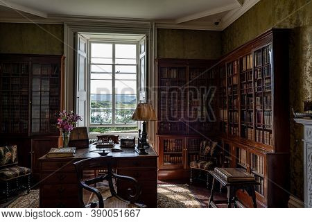 Old Library With A Desk And Vintage Lamp In A Historical Room With Bright Window