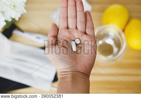 Senior Hand With Vitamin D, Vitamin C And Zinc On Background Of Wooden Table With Face Mask, Sanitiz