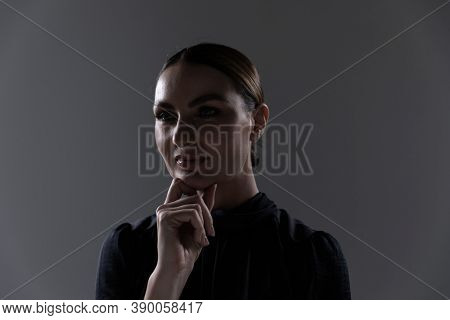 Portrait of an attractive confident Caucasian professional woman with long dark hair in a tidy bun wearing black, smart casual blouse with shadow on her face, on grey background.
