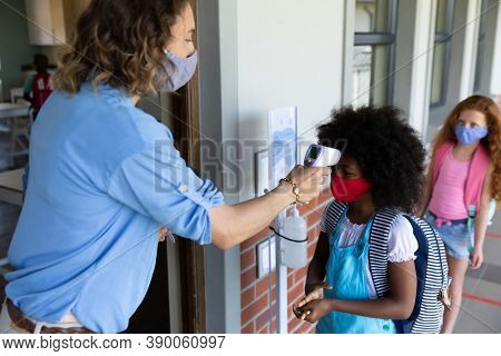 Multi ethnic group of school children wearing face masks, standing in line, having their temperature checked by a teacher. Education back to school health safety during Covid19 Coronavirus pandemic.