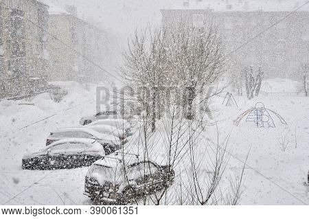 Heavy Blizzard In Town. Cars With Snow Covered On Parking Lot In Residential Area During December Sn