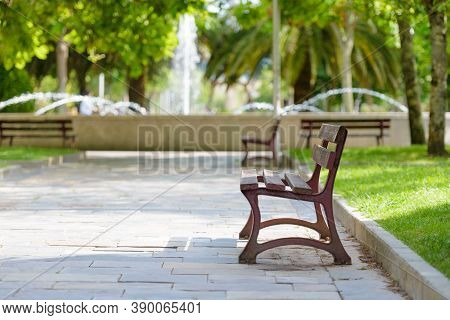 Wooden Bench In Empty City Park With Fountain