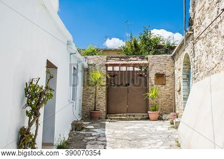 Stony Alleyway And Entrance To The House In Lefkara, Cyprus. Door Decorated With Plants In Pots Over