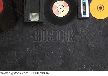 Musical Storage Devices And Copy Space. Old Audio Cassette Tapes, Compact Disc And Vinyl Record On W