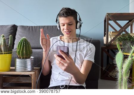 Handsome Smiling Teenager Boy In Headphones With Smartphone Making Video Call. Teenager Sitting At H