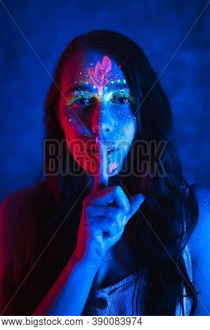 Beautiful Woman In With Fluorescent Makeup Holds Finger Near Her Lips. Fluorescent Paint In Neon Lig