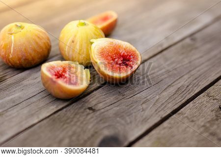 Fresh Fig Sliced In Half With Whole Figs In The Background, On A Wooden Surface. Fig Fruits On A Woo