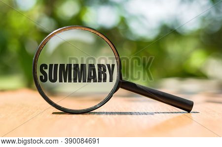 The Word Summary On Magnifier Glass On Wooden Table. Business Concept.