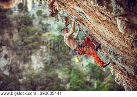 Young Male Rock Climber On Overhanging Wall. Rock Climbing On Natural Cliff. Strong Young Man Strugg