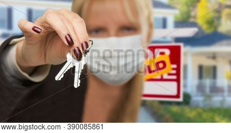 Woman Presenting House Keys Wearing Medical Face Mask.