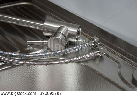 Installation Of The Kitchen Faucet To A Sink. A Kitchen Faucet Is Fitted With Hoses For Installation