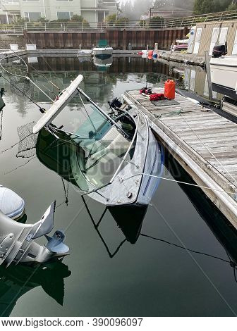 An Aluminum Fishing Boat Is Sinking At It's Slip On The Dock, And Is Filling Up With Water Quickly A