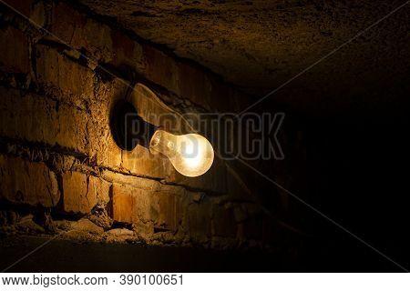 Light Bulb On Brick Wall. Light Bulb Glowing In Dark. Incandescent Light Bulb On A Dark Wall Backgro
