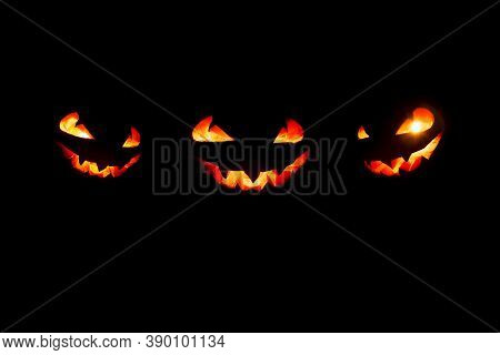 Three Halloween Pumpkin Glowing Faces In A Row On Black Background. Scary Halloween Pumpkins With Ey