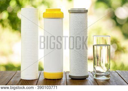 Water Filters. Carbon Cartridges And A Glass Of Water On Wooden Table On Nature Background. Househol