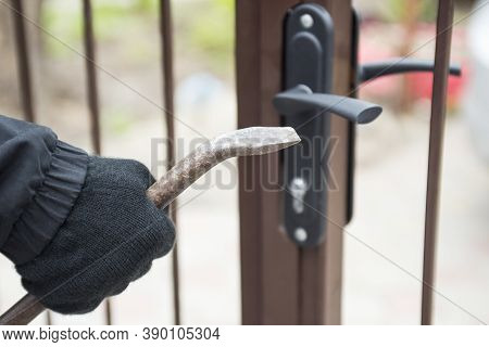 Burglar Trying To Break The Gate With A Crowbar. Burglar Trying To Force A Lock Using A Crowbar.