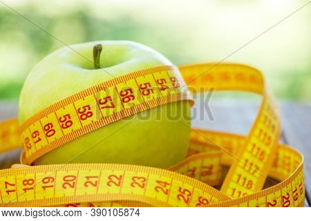 Green Apple With Measuring Tape On Wooden Background. Apples And Sewing Tape Measure On A Wooden Tab