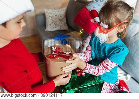 Little Cute Boy In Red Christmas Santa Claus Hat Gives Gift To Sister, Friend. Boxes With Bows.playi