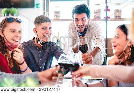 Friends Toasting Wine At Restaurant Wearing Face Masks - New Normal Lifestyle Concept With Happy Peo