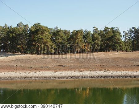 Beautiful Nature Landscape Green Forest Of Pine Tree Reflect On The Water Surface, Lake Backwater At