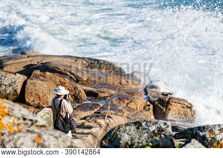 Portonovo, Spain - August 21, 2020: A Well-equipped Photographer Takes Pictures At Sunset From The R