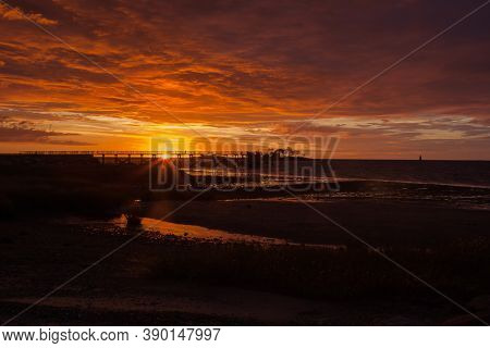 Fishing pier silhouette with sunris yellow colored sky