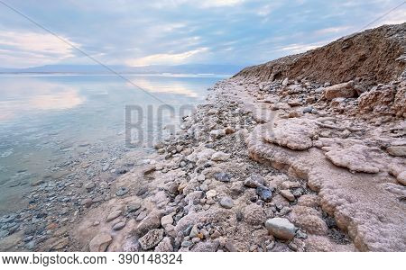 Sand And Stones Covered With Crystalline Salt On Shore Of Dead Sea, Clear Water Near - Typical Scene