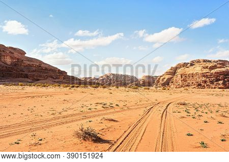 Rocky Massifs On Red Sand Desert, Vehicle Tracks Ground, Bright Cloudy Sky In Background, Typical Sc